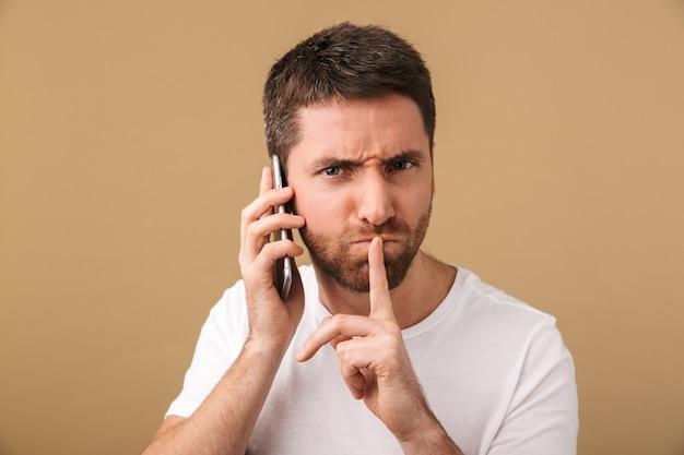 Poważny młody człowiek dorywczo rozmawia przez telefon komórkowy na białym tle, pokazując gest ciszy