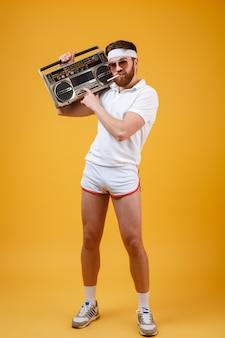 Poważny młody człowiek jest ubranym okulary przeciwsłonecznych trzyma magnetofon