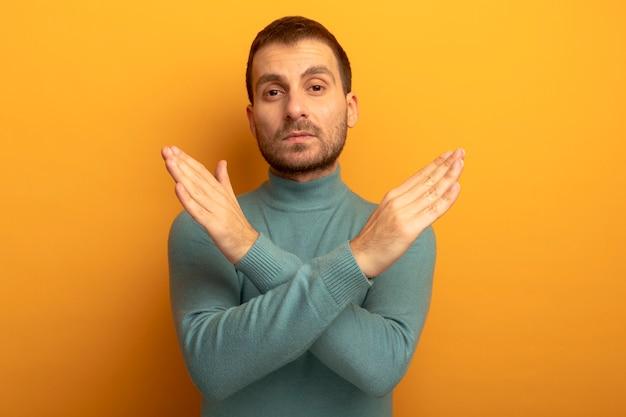 Poważny młody człowiek kaukaski patrząc na kamery nie robi żadnego gestu na białym tle na pomarańczowym tle z miejsca na kopię