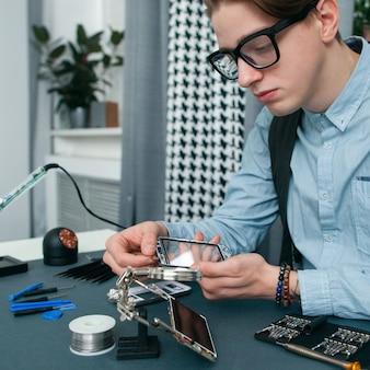 Poważny młody człowiek naprawiający telefon komórkowy wolnego miejsca.