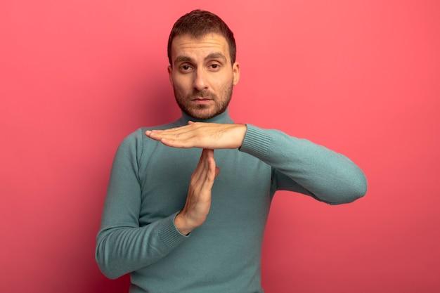 Poważny młody człowiek patrząc z przodu robi gest limitu czasu na białym tle na różowej ścianie