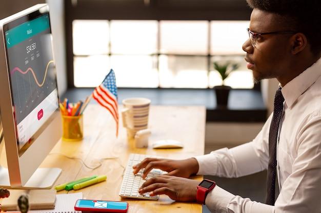 Poważny młody człowiek patrzący na ekran komputera podczas sprawdzania statystyk finansowych