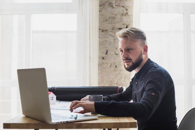 Poważny młody człowiek pracuje na laptopie przy biurem