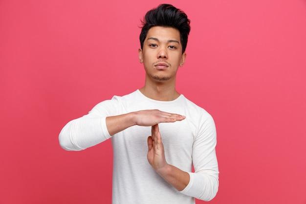 Poważny młody człowiek robi gest limitu czasu