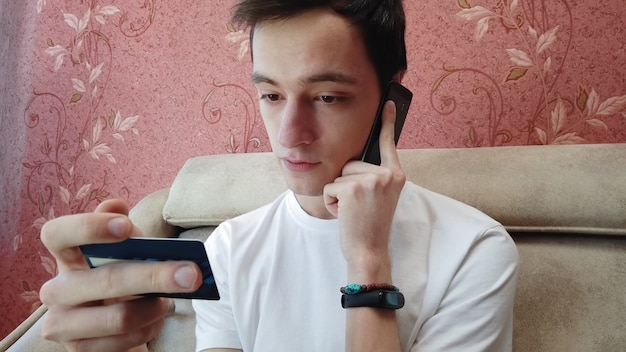 Poważny młody człowiek rozmawia przez telefon na zakupy online