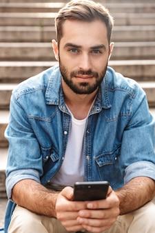 Poważny młody człowiek siedzący na schodach na zewnątrz, korzystający z telefonu komórkowego