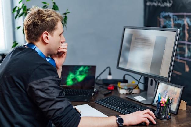 Poważny młody człowiek skoncentrował się na problemie na ekranie komputera. inteligentny programista ciężko pracuje w firmie it wewnątrz budynku.