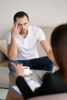 Poważny młody człowiek słucha żeńskiego psychologa, doradcy lub konsultanta