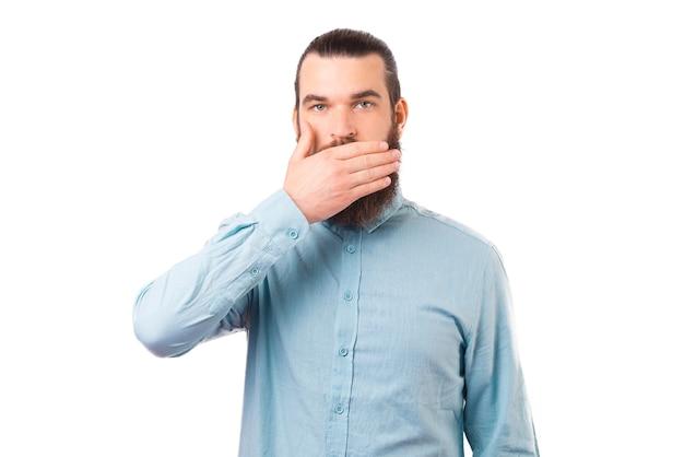 Poważny młody człowiek stoi na białym tle, zakrywając usta.