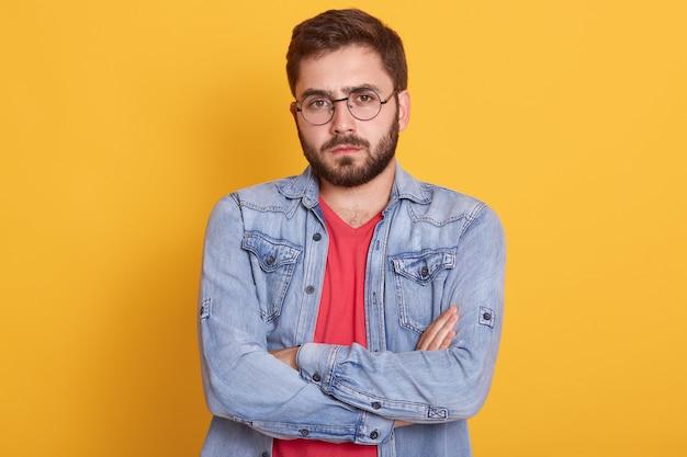 Poważny młody człowiek stojący z założonymi rękami i z gniewnym wyrazem twarzy
