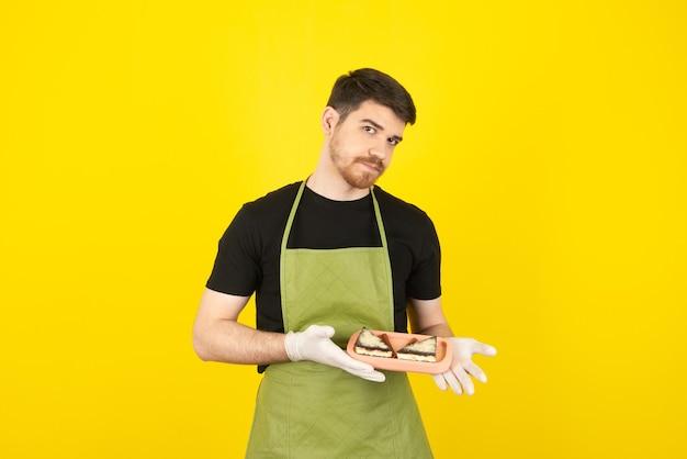 Poważny młody człowiek trzyma plastry ciasta i patrząc na kamery.