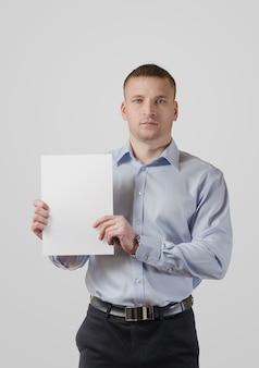 Poważny młody człowiek trzyma pusty sztandar lub kartę. na białym tle na białej powierzchni