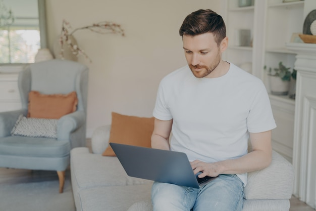 Poważny młody człowiek używający laptopa do pracy zdalnej z domu, skoncentrowany freelancer czytający przychodzące e-maile lub rozmawiający online, badający lub uczący się, siedząc na kanapie w salonie