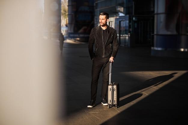Poważny młody człowiek w czarnych ubraniach czeka na stacji
