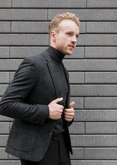 Poważny młody człowiek w czerni blisko szarej ściany