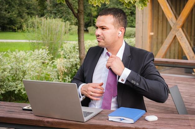Poważny młody człowiek w garniturze zdejmuje krawat po skończonej pracy na otwartej werandzie