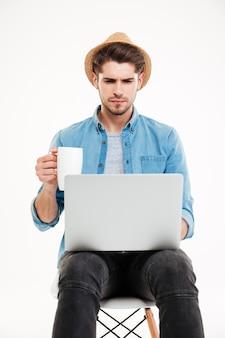 Poważny młody człowiek w kapeluszu pijący kawę i używający laptopa