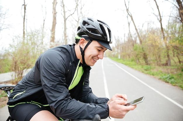 Poważny młody człowiek w kasku ochronnym z rowerem przy użyciu telefonu komórkowego