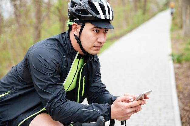 Poważny młody człowiek w kasku rowerowym z rowerem za pomocą telefonu komórkowego