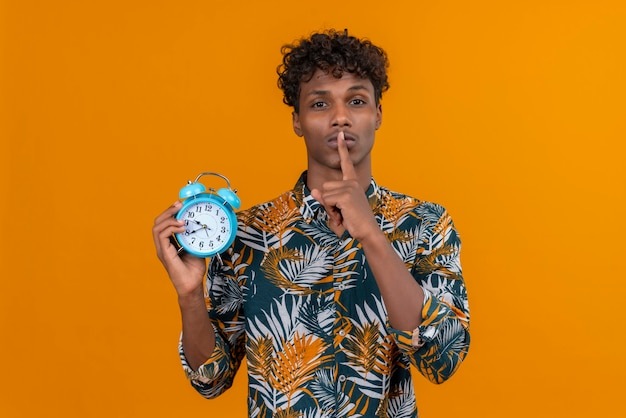 Poważny młody człowiek w koszuli pokazując gest shh z palcem wskazującym w pobliżu ust, trzymając budzik na pomarańczowym tle