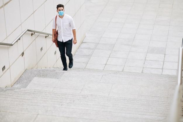 Poważny młody człowiek w masce medycznej chodzący po schodach w mieście