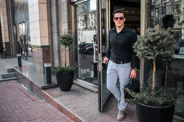 Poważny młody człowiek wychodzi na zewnątrz budynku. on otwiera drzwi. facet trzyma w ręku czarną torbę.