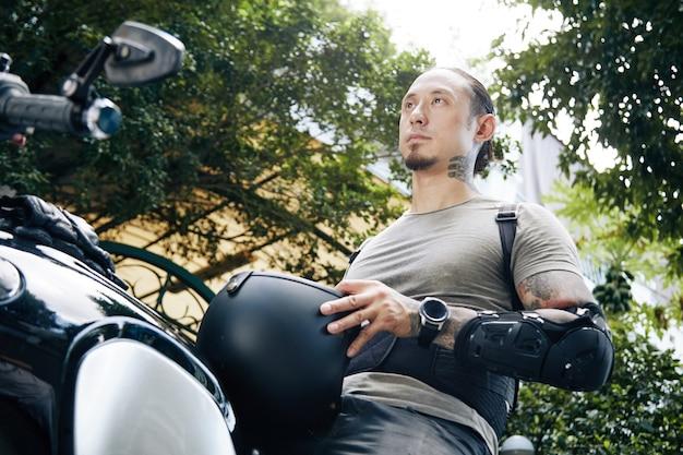 Poważny młody człowiek z kaskiem siedzi na motocyklu i zdejmuje kask