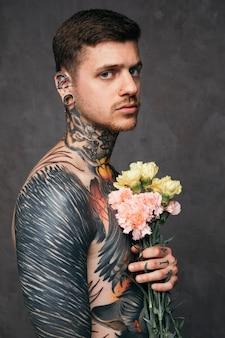 Poważny młody człowiek z przebitym nosem i uszami trzyma kwiaty goździków w ręku stojąc na szarym tle