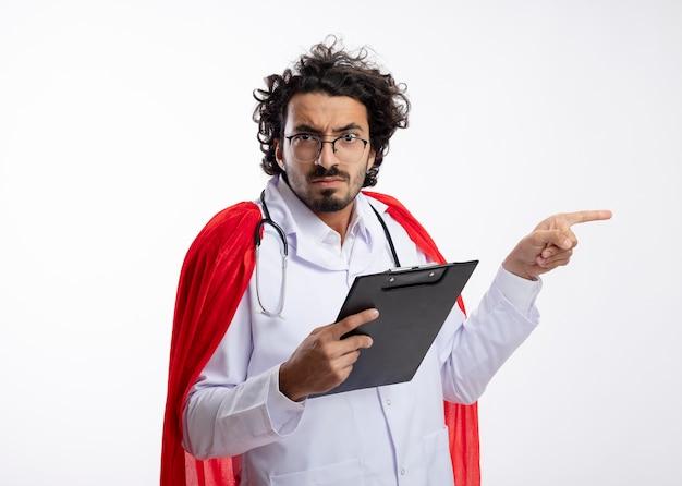 Poważny młody kaukaski mężczyzna superbohatera w okularach optycznych w mundurze lekarza z czerwonym płaszczem i stetoskopem na szyi trzyma schowek i wskazuje z boku z miejscem na kopię