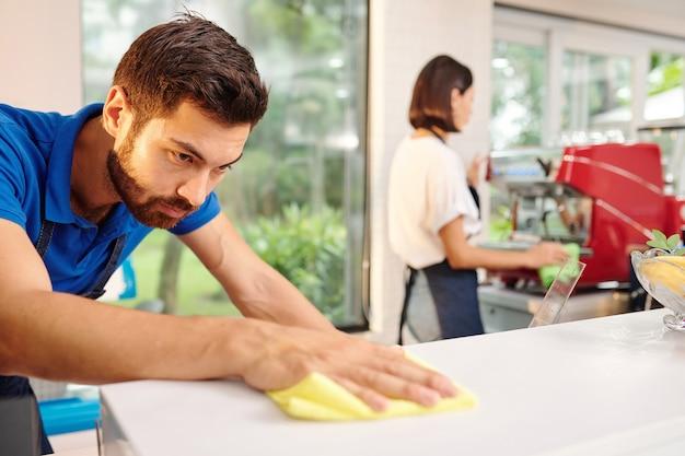Poważny młody kelner w kawiarni lub barista czyszczący powierzchnię klienta za pomocą detergentu dezynfekującego