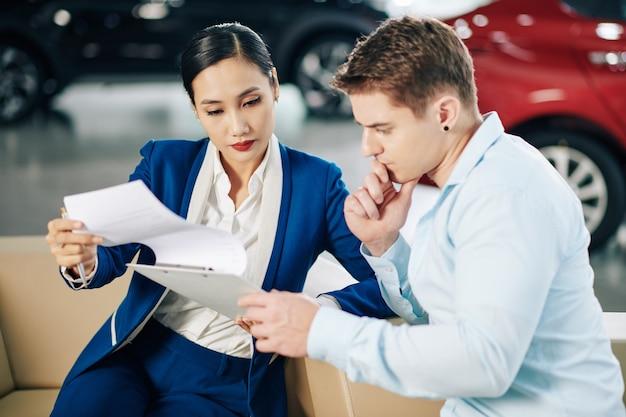 Poważny młody klient uważnie czytający umowę w rękach menadżera salonu samochodowego