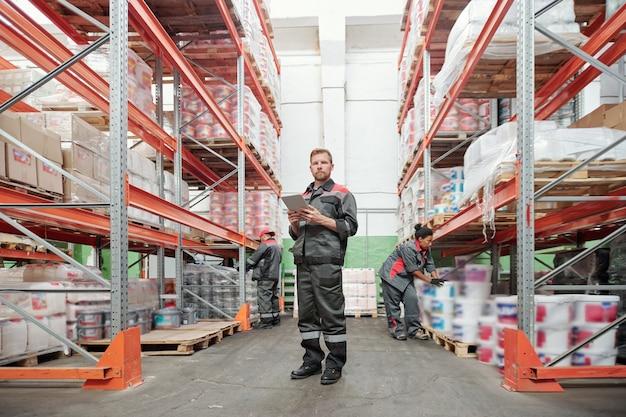 Poważny młody mężczyzna pracownik magazynu w mundurze za pomocą tabletu stojąc w przejściu między regałami