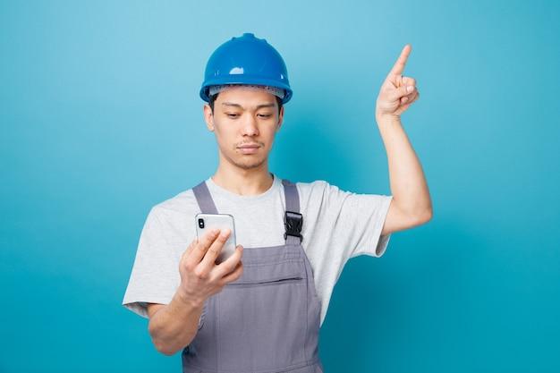 Poważny młody pracownik budowlany w kasku ochronnym i mundurze, trzymając i patrząc na telefon komórkowy skierowaną w górę
