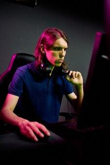 Poważny młody programista skupiony na problemie z komputerem, noszący słuchawki na szyi, pracujący w ciemnym biurze
