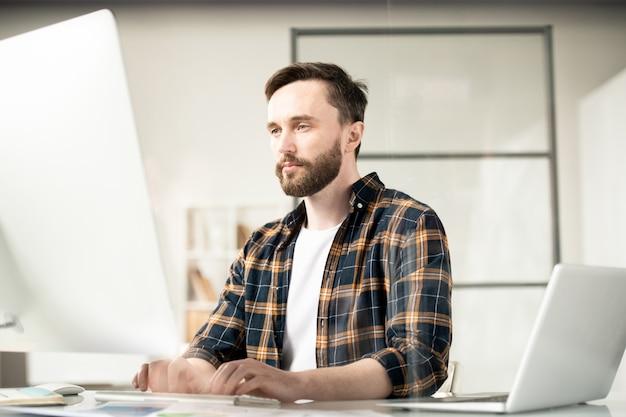 Poważny młody projektant stron internetowych koncentrujący się na przeglądaniu informacji online, siedząc przed ekranem komputera
