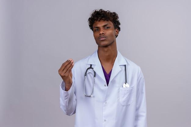 Poważny młody przystojny ciemnoskóry lekarz z kręconymi włosami, ubrany w biały fartuch ze stetoskopem podnoszącym rękę