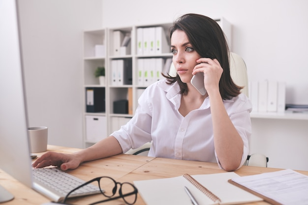 Poważny młody sekretarz lub kierownik biura siedzi przy biurku przed ekranem komputera, rozmawia przez telefon i pracuje z danymi