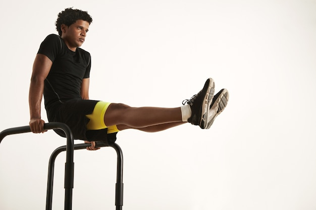 Poważny młody, sprawny afroamerykanin w czarnej odzieży sportowej, siedzący w pozycji l na krótkich barach w domu przy białej ścianie
