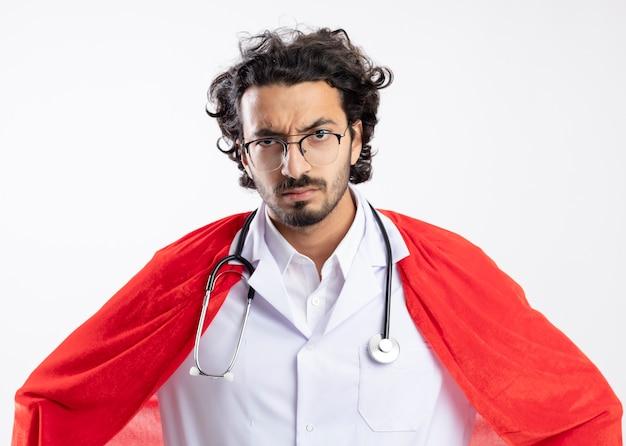 Poważny młody superbohater kaukaski mężczyzna w okularach optycznych, ubrany w mundur lekarza z czerwonym płaszczem i stetoskopem wokół szyi