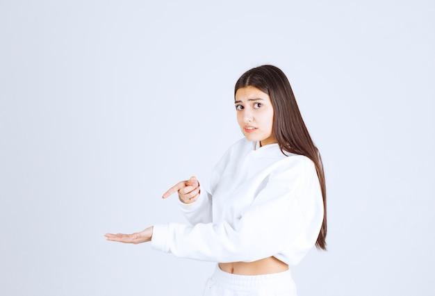 Poważny model dziewczyny, wskazując na jej dłoń.