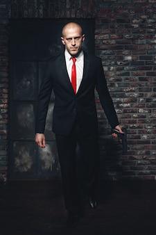 Poważny morderca najemny w czerwieni, trzymający broń
