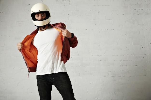 Poważny motocyklista pokazuje pomarańczową podszewkę swojej bordowej kurtki powietrznej w zabytkowym kasku na białym tle
