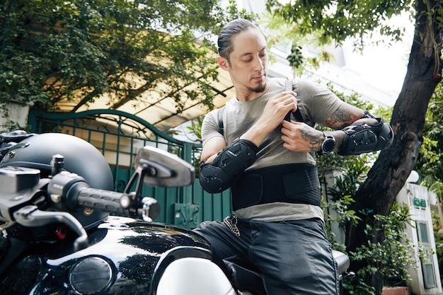 Poważny motocyklista zakładający pas nerkowy, ochraniacze na przedramiona i ochraniacz pleców przed jazdą