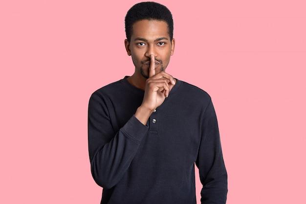 Poważny murzyn trzyma palec wskazujący na ustach, demonstruje delikatny gest, ubrany w swobodny sweter, mówi tajne informacje, dzieli się plotkami na różowo. ćśś, nie zdradzaj mojego sekretu