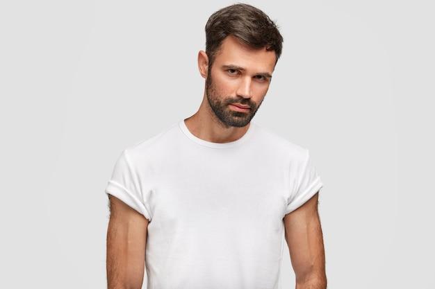 Poważny, muskularny młody mężczyzna z ciemnym zarostem, włosami, ubrany w zwykły biały t-shirt, ma muskularne ciało, uważnie czegoś słucha, odizolowany na białej ścianie. zarośnięty facet stoi w domu