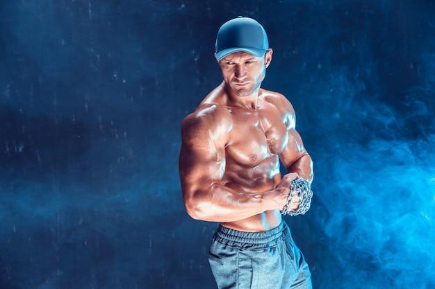 Poważny muskularny wojownik w czapce z łańcuchami zaplatanymi w dym w pięść