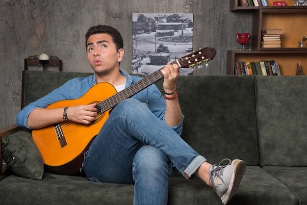 Poważny muzyk trzymający piękną gitarę i siedzący na kanapie