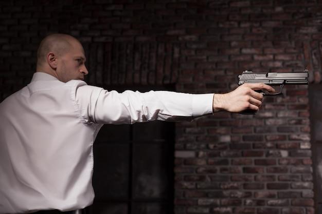 Poważny najemny morderca w czerwonym krawacie wyceluje broń