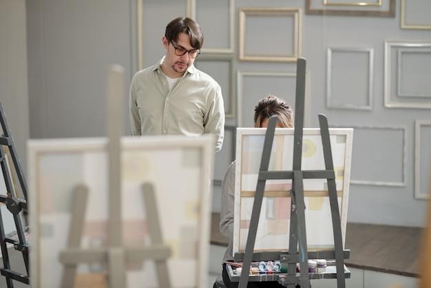 Poważny nauczyciel profesjonalnego kursu malarstwa w towarzystwie jednego ze swoich uczniów, który na lekcji pracuje nad nowym dziełem sztuki