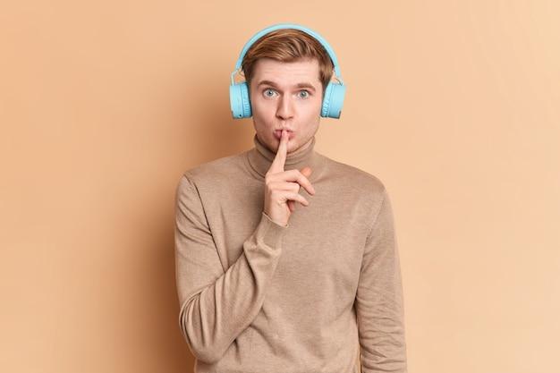Poważny, niebieskooki młody mężczyzna wykonuje gest uciszenia, trzymając palec wskazujący na ustach, pokazuje znak ciszy, prosząc o ciszę, słucha muzyki w słuchawkach, nosi swobodny golf